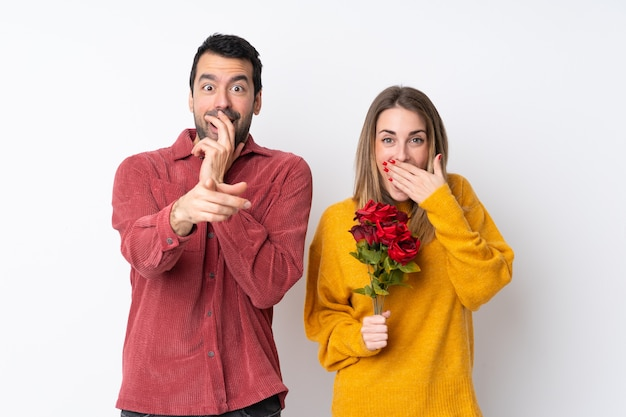 Couple in valentine day holding flowers over isolated wall pointing with finger at someone and laughing