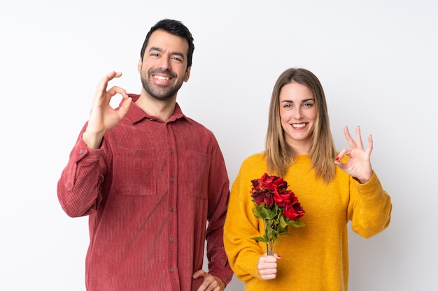 Couple in valentine day holding flowers over isolated wall showing an ok sign with fingers