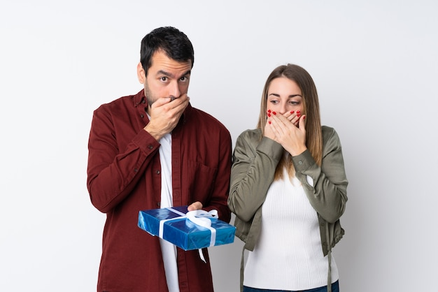 Couple in valentine day holding a gift over isolated wall covering mouth with hands