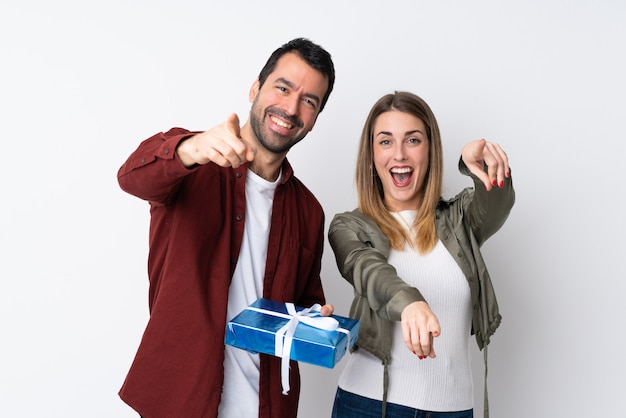 Couple in valentine day holding a gift over isolated wall points finger at you with a confident expression