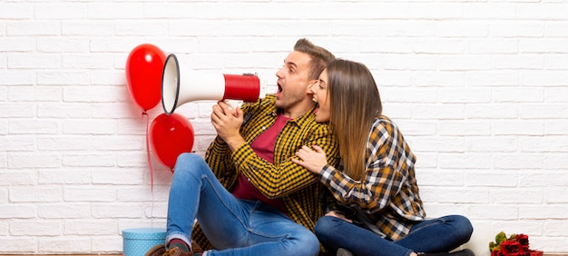 Couple in valentine day at indoors shouting through a megaphone