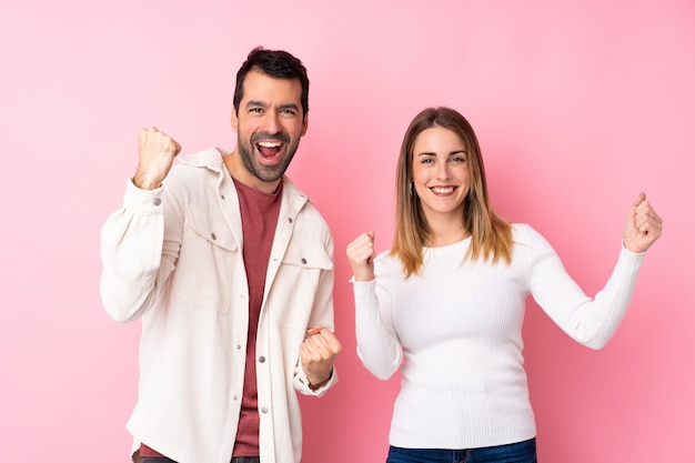 Couple in valentine day over isolated pink wall celebrating a victory