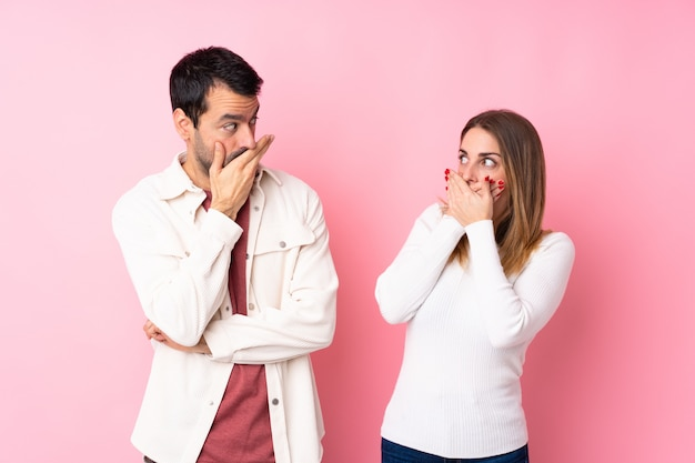 Couple in valentine day over isolated pink wall covering mouth with hands for saying something inappropriate