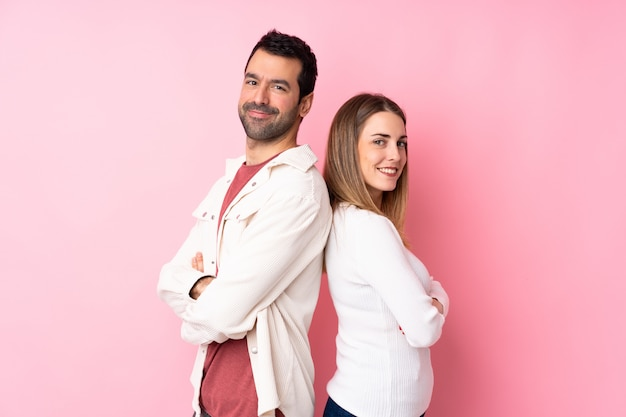 Couple in valentine day over isolated pink wall keeping the arms crossed in lateral position while smiling