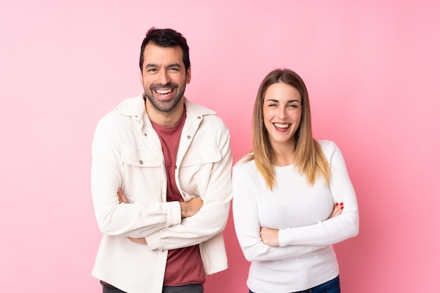 Couple in valentine day over isolated pink wall keeping the arms crossed while smiling