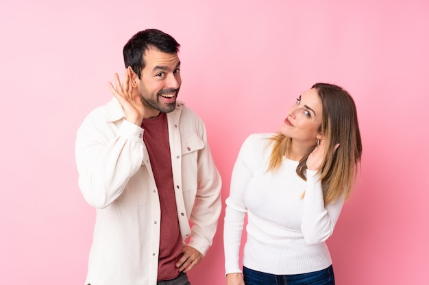 Couple in valentine day over isolated pink wall listening to something by putting hand on the ear