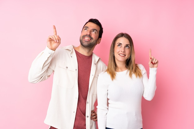 Couple in valentine day over isolated pink wall pointing a great idea and looking up