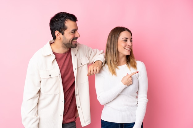 Couple in valentine day over isolated pink wall pointing to the side to present a product