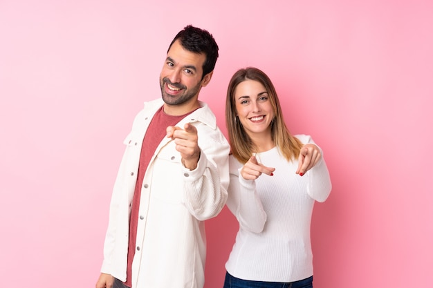 Couple in valentine day over isolated pink wall points finger at you while smiling