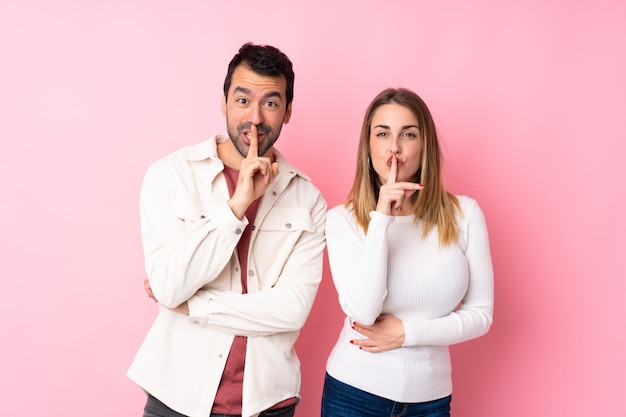 Couple in valentine day over isolated pink wall showing a sign of silence gesture putting finger in mouth