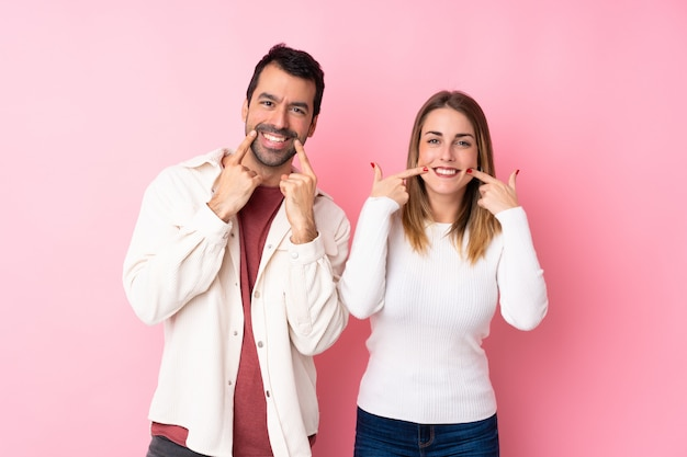 Couple in valentine day over isolated pink wall smiling with a happy and pleasant expression