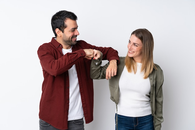 Couple in valentine day over isolated wall bumping fists