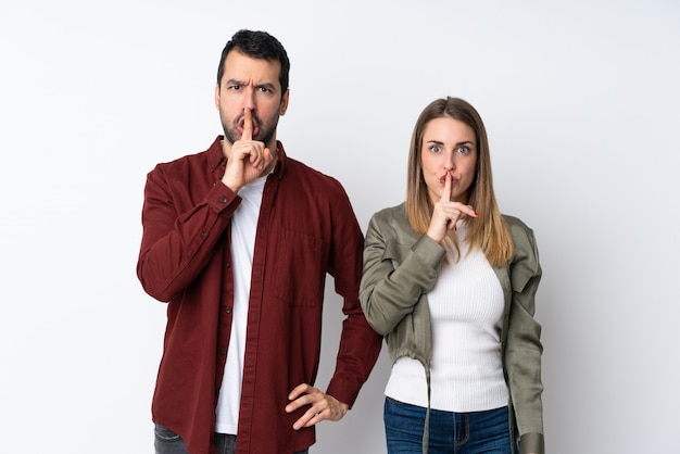 Couple in valentine day over isolated wall showing a sign of closing mouth and silence gesture