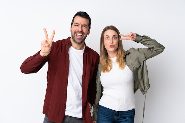 Couple in valentine day over isolated wall smiling and showing victory sign