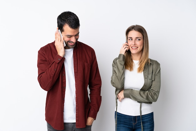 Couple in valentine day over isolated wall talking to mobile