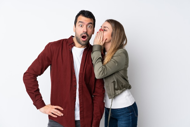 Couple in valentine day over isolated wall whispering something