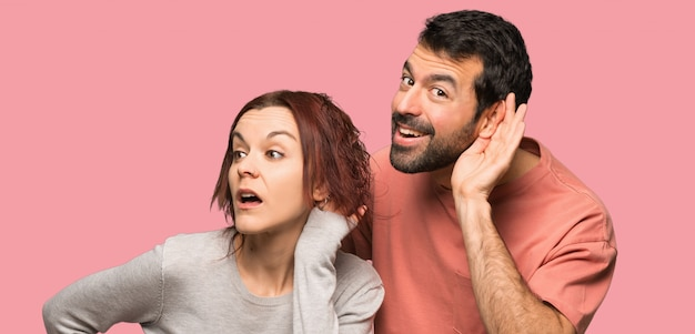 Couple in valentine day listening something over isolated pink background