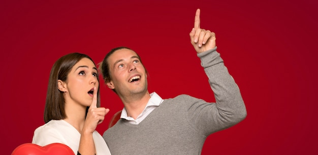 Couple in valentine day pointing up and surprised over red background