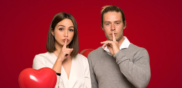Couple in valentine day showing a sign of silence gesture putting finger in mouth