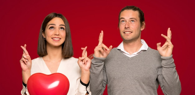 Couple in valentine day with fingers crossing and wishing the best over red background