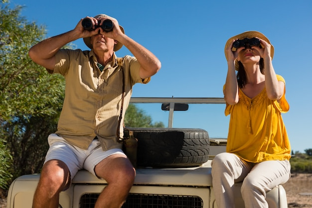 Couple in vehicle looking through binoculars while sitting on vehicle hood