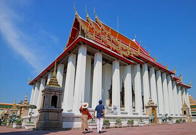 Couple visiting wat pho or temple of the reclining buddha, bangkok, thailand