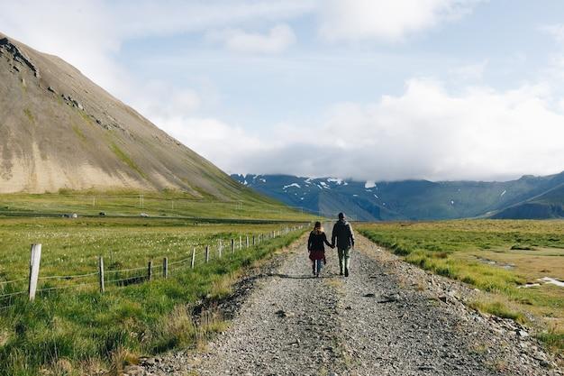 カップルは田舎の砂利道を歩く