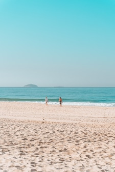 Couple walking along the shore on a sunny beach with a cloudless sky above