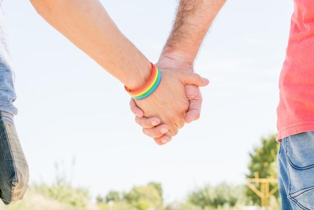 通りを歩いて、手を繋いでいるカップル
