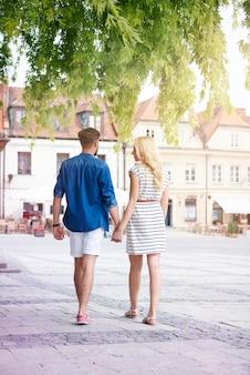 夏の日に旧市街を歩くカップル