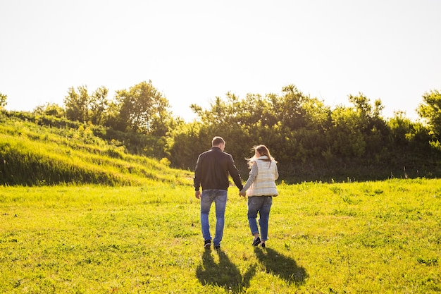 Couple walking in autumn sunset countryside meadow holding hands.