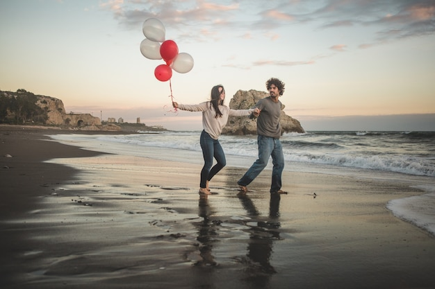 Couple walking barefoot by the shore of the beach