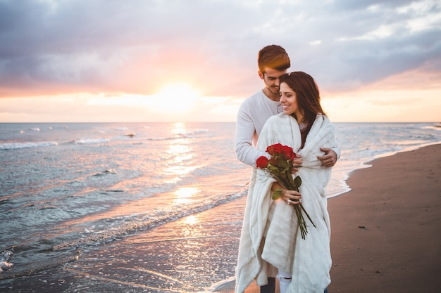 Couple walking on the beach with a bouquet of roses at sunset