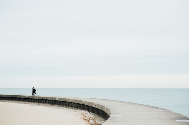 A couple walking on the bridge  with sand and lake at chicago, il.