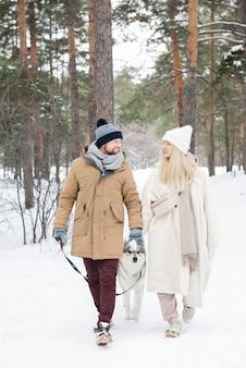 冬の日に犬を歩くカップル
