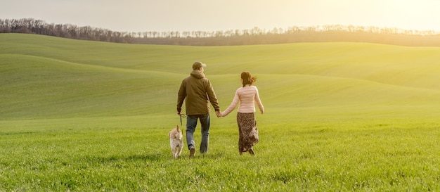 Couple walking dog on spring field