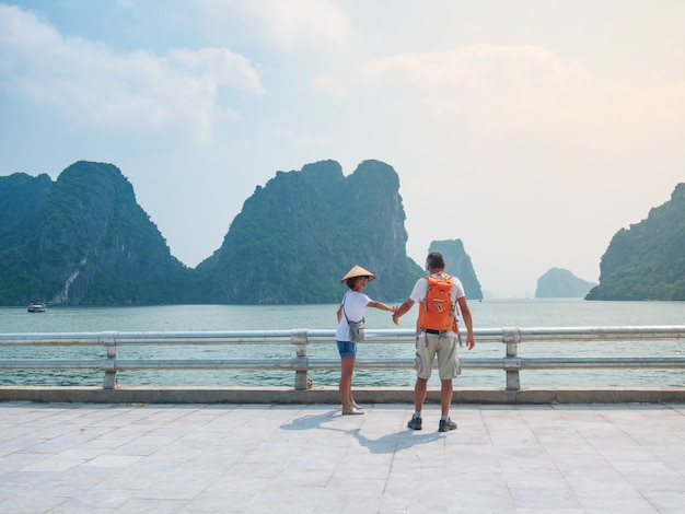 Couple walking hand in hand on promenade at halong city, vietnam, view of ha long bay rock pinnacles in the sea. man and woman having fun traveling together on vacation to famous landmark.