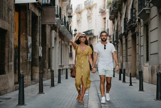 Пара гуляет, держась за руки в старом городе испании. парочка туристов на свидании в валенсии.