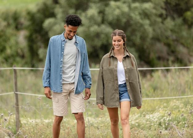 自然の中を歩くカップルミディアムショット