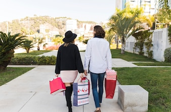 Couple walking in park with shopping bags