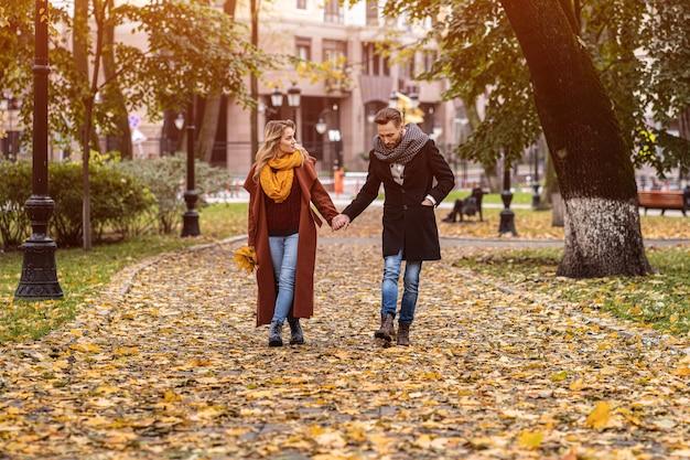 Пара гуляет в парке, держась за руки
