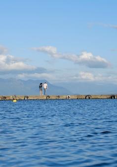 Пара гуляет на пирсе возле пляжа в летний день, голубое небо и вода. праздник и летняя концепция
