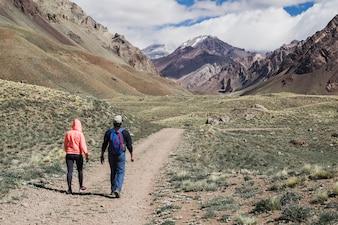 Couple walking on dirt track near mountain range