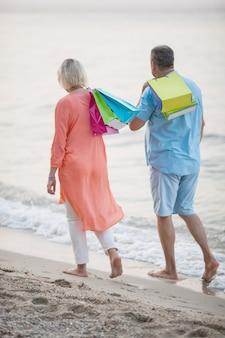 Пара прогулки по пляжу после отдыха