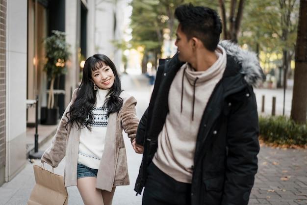 Пара гуляет по улице с сумкой для покупок