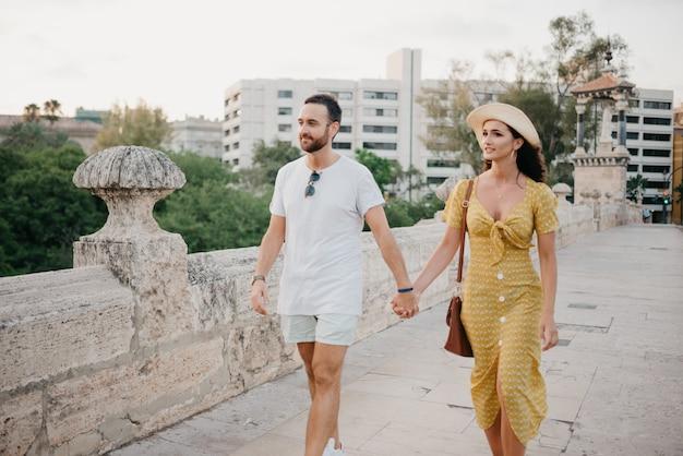 Пара, идущая по древнему мосту в старом городе испании. пара туристов на свидании в валенсии