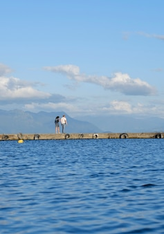 Couple walking on a pier near the beach on a summer day, blue sky and water. holiday and summer concept