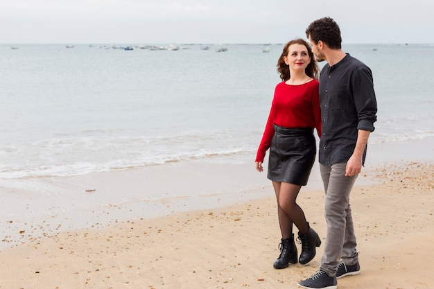 Couple walking and talking on sea shore
