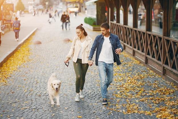 晴れた秋の日に犬を歩いているカップル