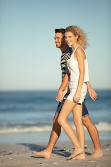 Couple walking together hand in hand on the beach